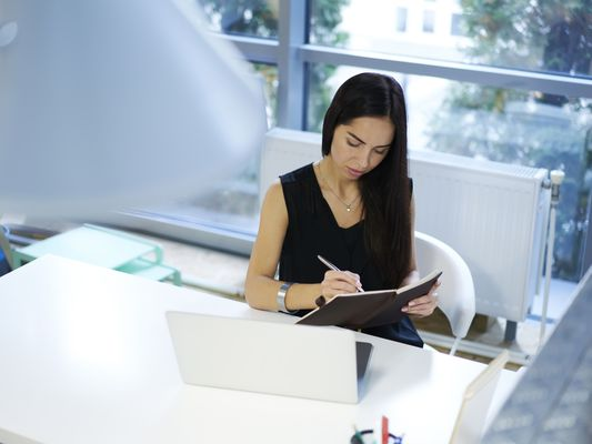 young woman writing in a planner while sitting in front of a laptop