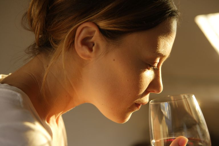 Woman holding wine glass, smelling, side view, close up