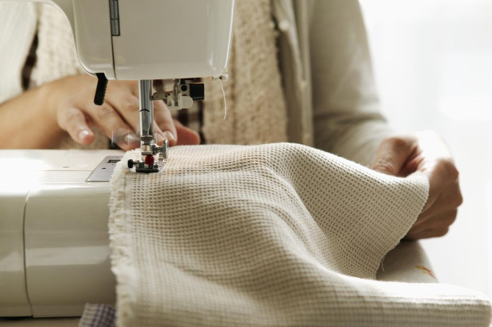 Woman using sewing machine on table, close up, mid section