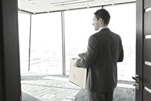 Businessman carrying cardboard box in office