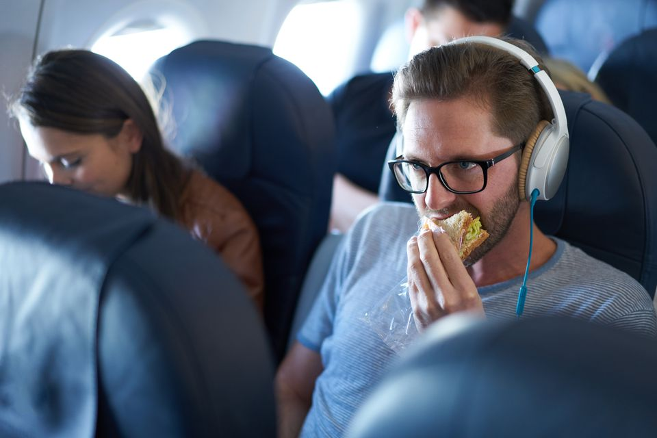 man eating sandwich on flight