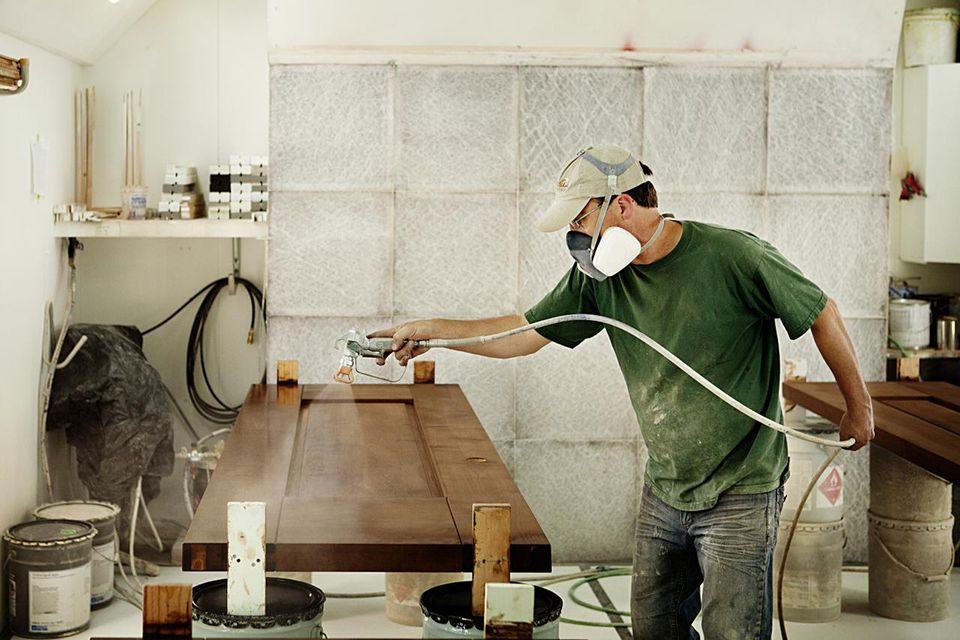 Carpenter Wearing Mask and Spraying Finish on Wood