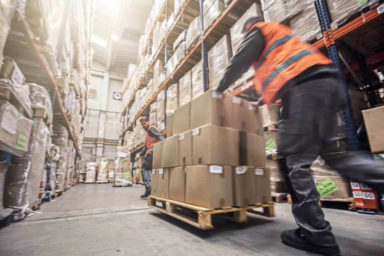 Two men moving a skid of boxes through a warehouse