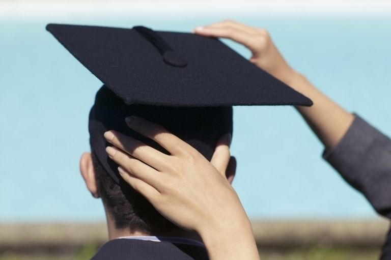graduation cap being placed on young man's head