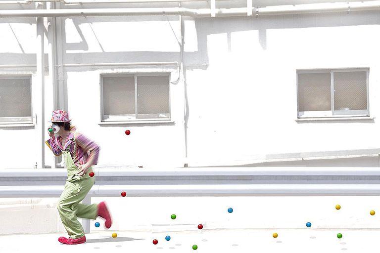 The clown runs while dropping a ball