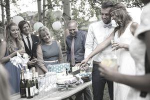 Bride and groom cutting cake backyard wedding reception
