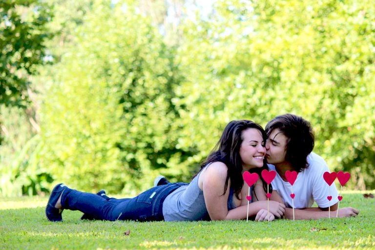 affectionate teen couple lying on grass