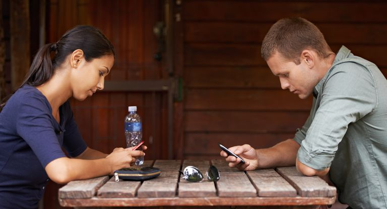 man and woman at a table looking at their phones