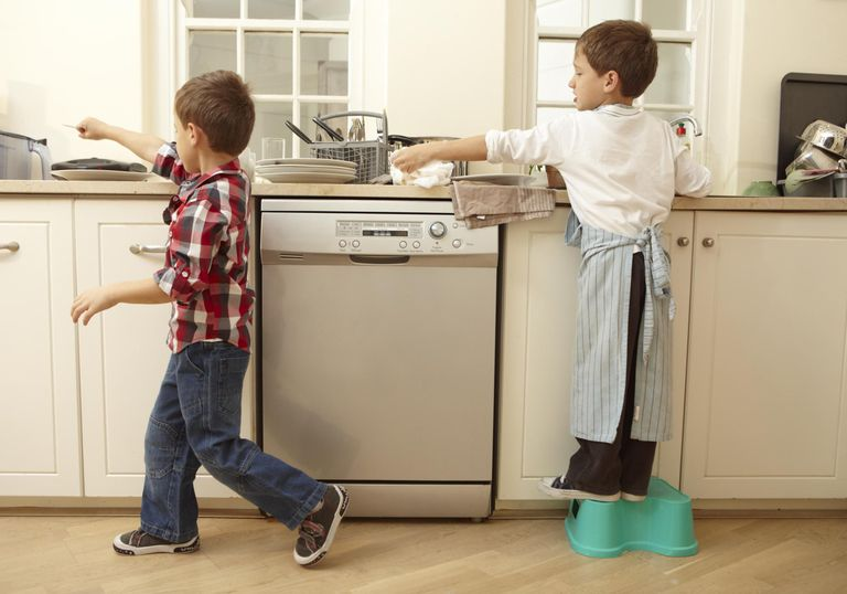 Twin boys passing cutlery while washing dishes.