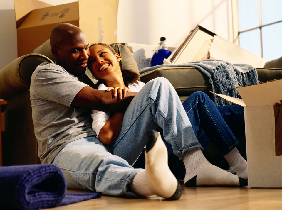 Happy African American couple with opened moving boxes sitting on the floor