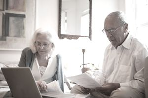 Senior couple using latop in home