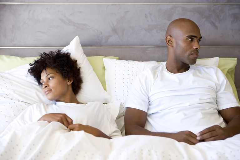 Young couple in bed, looking away from each other