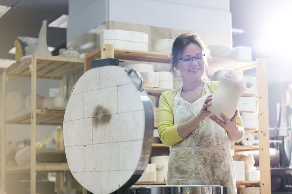Smiling mature woman placing pottery vase in kiln in studio