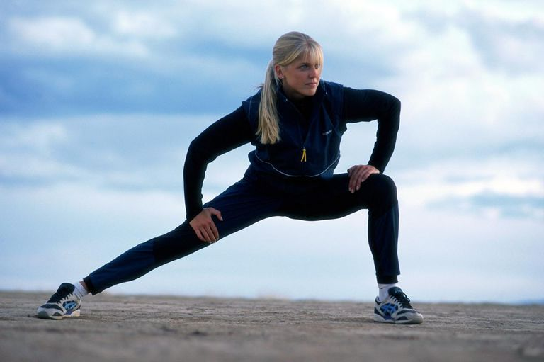 woman stretching after warming up and before running