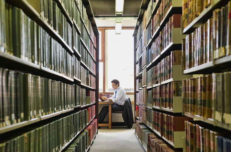 Hispanic businessman doing research in library