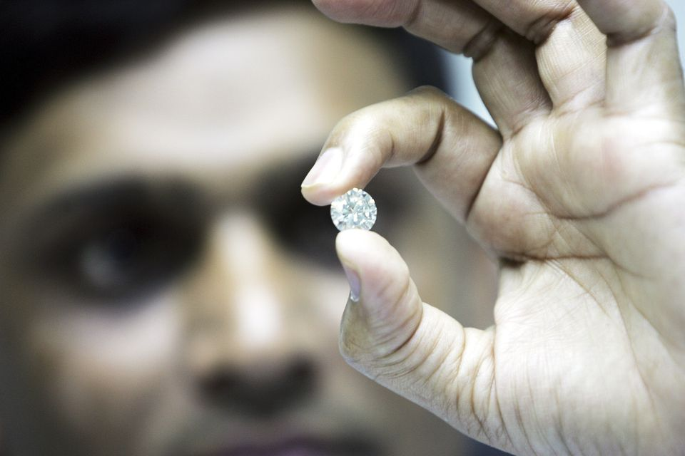 A diamond worker in India examining a piece of diamond.