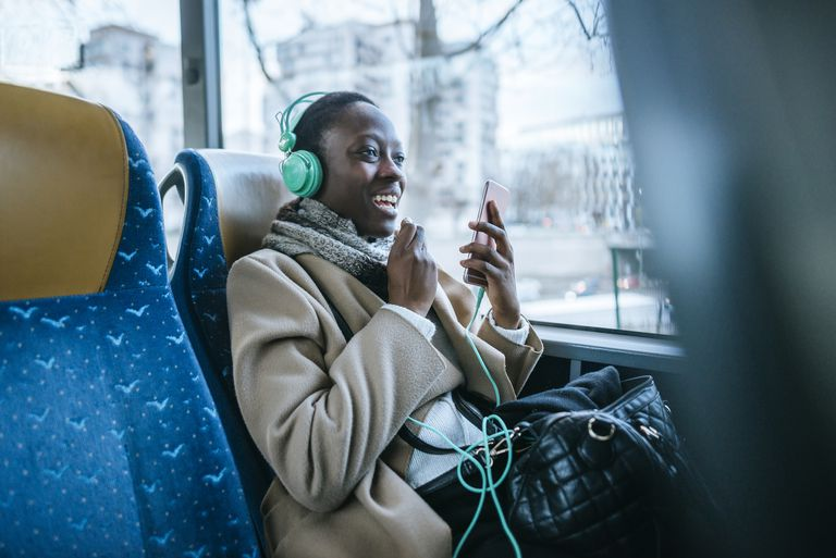 Young woman using headphones and smartphone in a bus