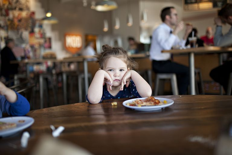 a child with elbows on the table during a meal