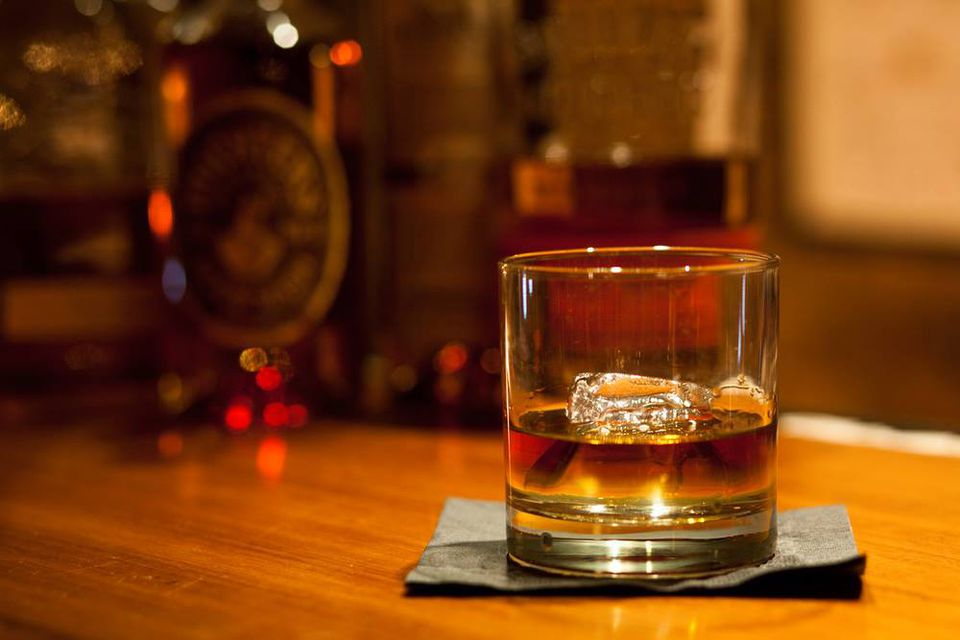 A glass of bourbon with ice on a bar
