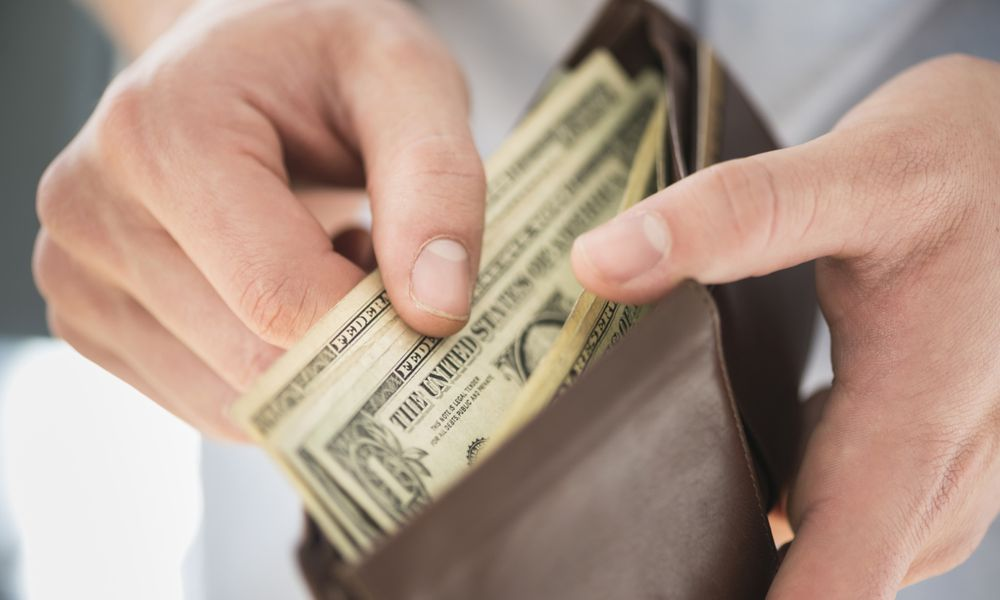 Man Counting Cash in Wallet
