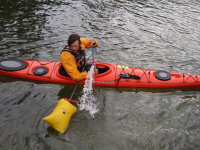 A kayak instructor demonstrates how to use a paddle float and bilge pump.