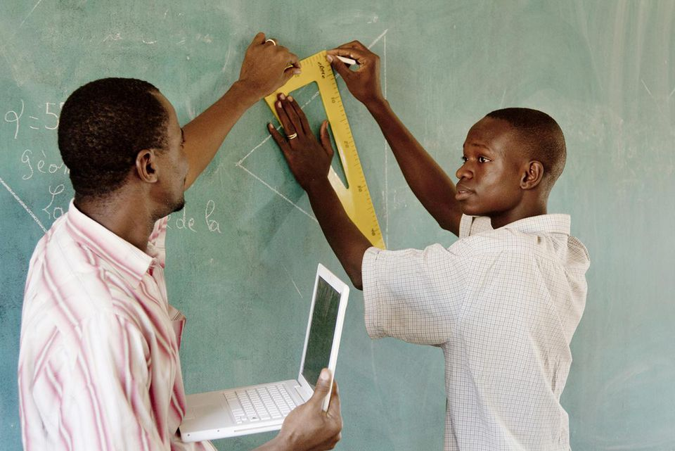 Teacher with laptop helps a student in front of chalkboard