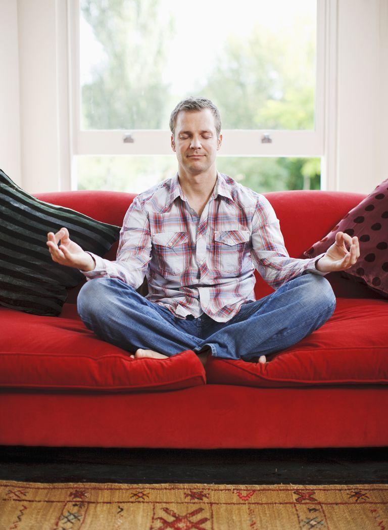 Man meditating on sofa