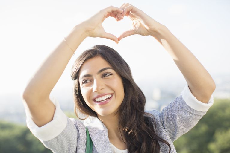 Woman making heart-shape with hands outdoors