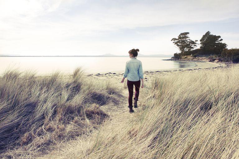 Woman walking onto beach in winter