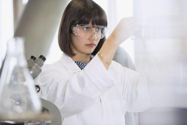 Female college student conducting scientific experiment in science laboratory classroom