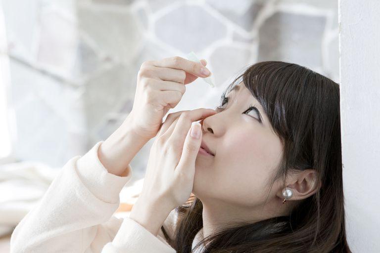 Young woman applying eye drops