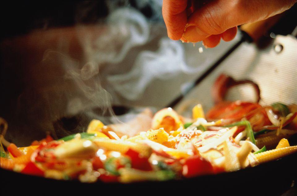 Stir-fried vegetables, close-up of hand sprinkling seasoning