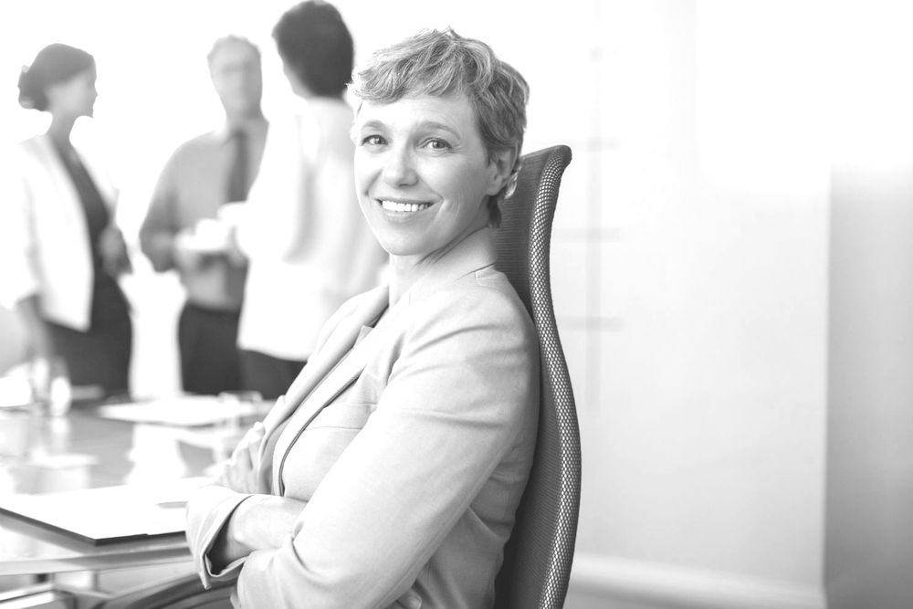 Business professional sitting in armchair while project team is in background