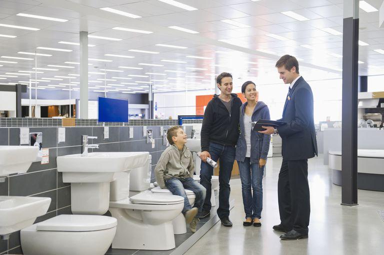 Salesman talking to Hispanic family in bathroom supply store