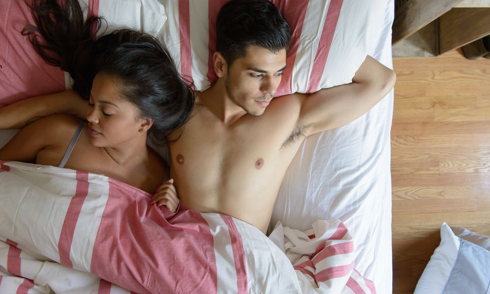 man and woman lie in bed, the woman is asleep the man is awake and thinking.