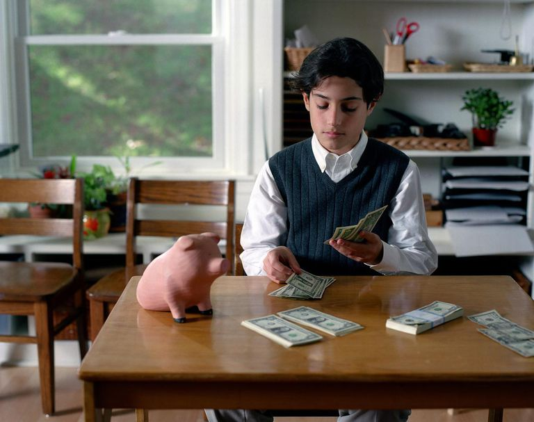 Boy (10-12) at desk counting US money
