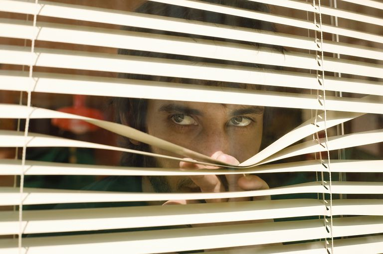Young man peeping through window blinds