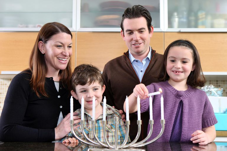 Family lighting the menorah