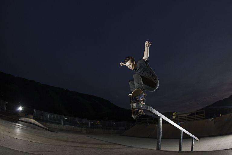Skateboader at a skate park, jumping over a rail.