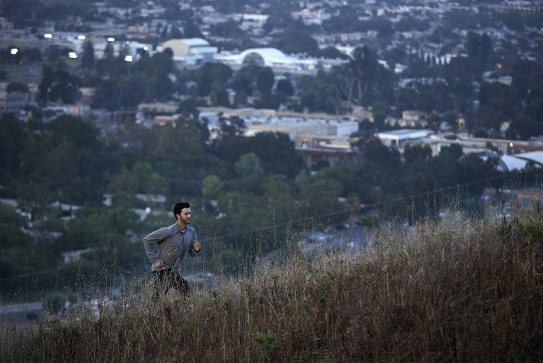 Male Trail Runner running up a hill