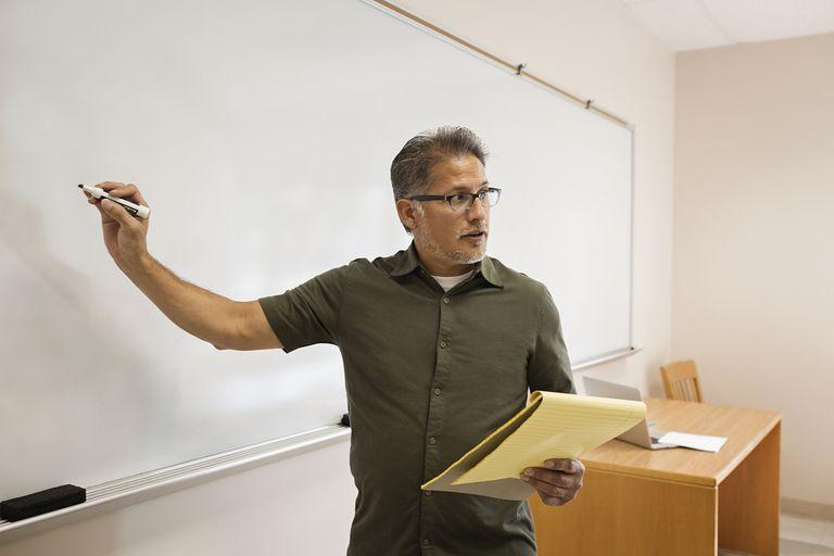 Professor writing on whiteboard in classroom