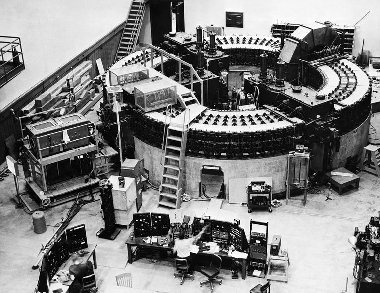 Black and white photograph of a large circular structure, with computer monitors surrounding it.