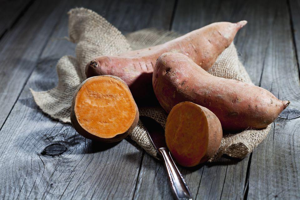 Row sweet potatoand knife on jute, wood