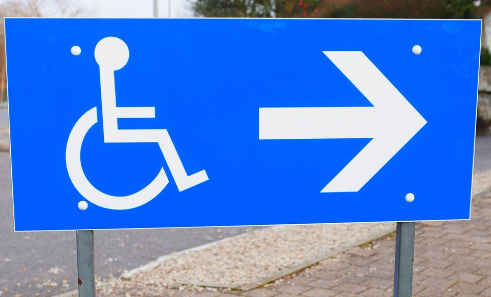 A blue sign has white icons of a wheelchair and an arrow.