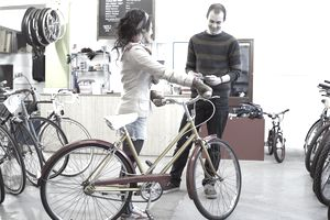 Woman with bicycle in bike shop.