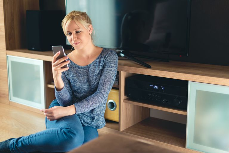 A woman sitting in front of a home theater system while holding a smartphone