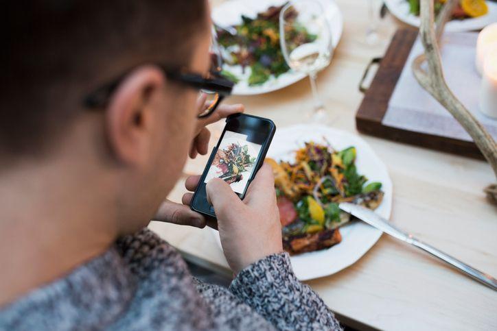 Man Taking Photo of Meal