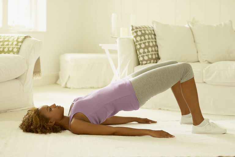 Woman in leggings and sleeveless top performing back bridge stretching exercise, lying on floor, side view