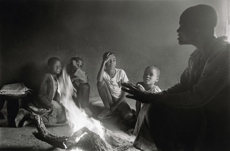 woman telling story to children around a fire