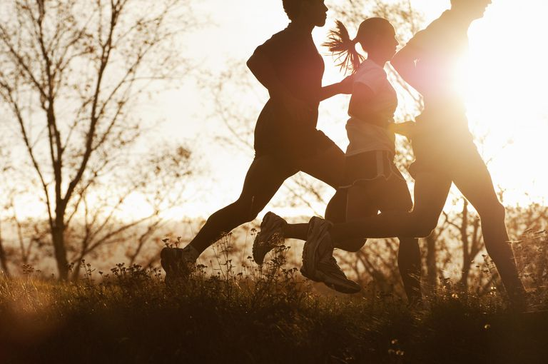 Three people running in the late afternoon.